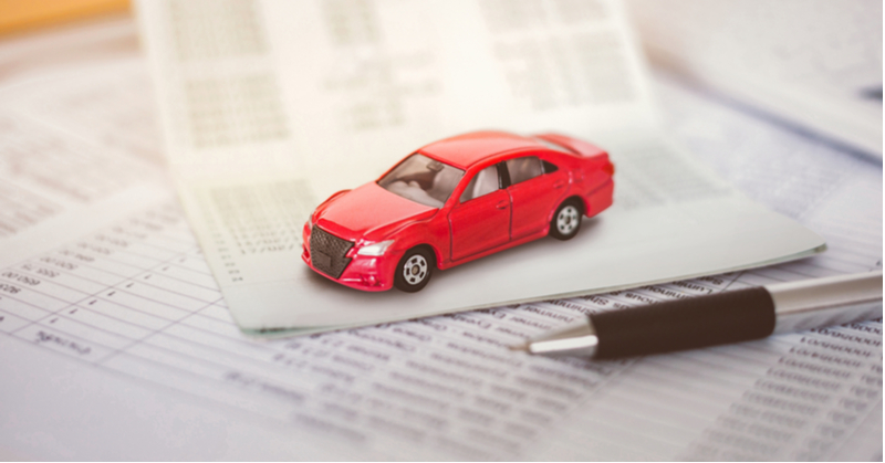 Toy car sitting on top of accounting paperwork